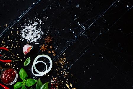 vysoký úhel pohledu: Rajčatová omáčka, čerstvé bylinky a koření, plátky cibule a feferonek na tmavém vintage pozadí s prostorem pro text.