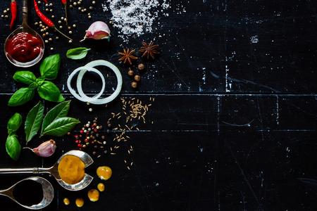 Verschillende soorten sauzen, verse kruiden en specerijen op donkere uitstekende achtergrond met ruimte voor tekst.