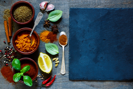 Slate background with spices and herbs. Cooking ingredients. Food and cuisine concept.