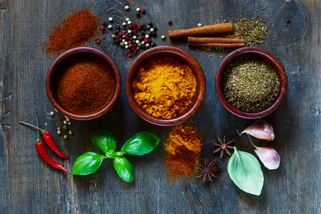 Assorted spices and herbs over dark old wood. Food and cuisine ingredients. Cooking background.