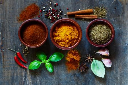Diverse specerijen en kruiden over donker oud hout. Voedsel en keuken ingrediënten. Koken achtergrond.