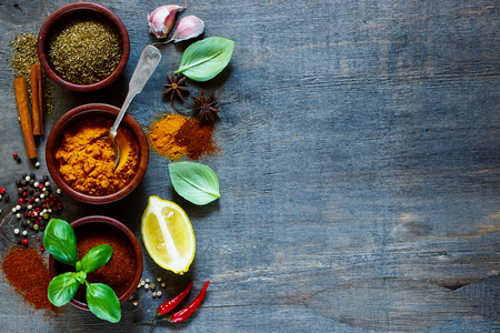 Various kind of spices and herbs over dark old wood. Food and cuisine ingredients. Background with space for text.