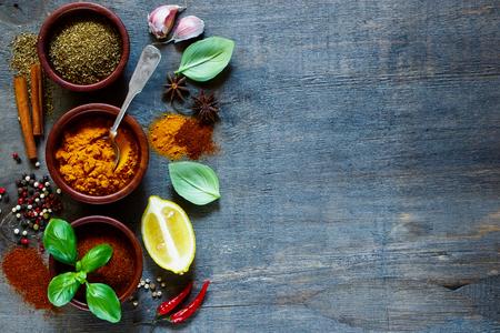 Diversos tipos de especias y hierbas sobre la madera vieja y oscura. Alimentos e ingredientes de cocina. Fondo con el espacio para el texto. Foto de archivo - 49746331
