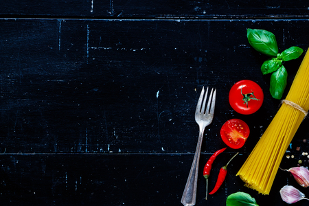 menu background: Ingredients for italian pasta (spaghetti, basil leaves, tomatoes, herbs) on dark vintage background with space for text. Vegetarian food, diet, health or cooking concept. Stock Photo