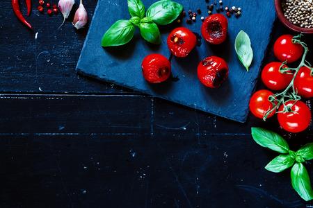 テキストのためのスペースと暗いヴィンテージ背景に焼きミニトマト。ベジタリアン料理、食事療法、健康や料理の概念。 写真素材