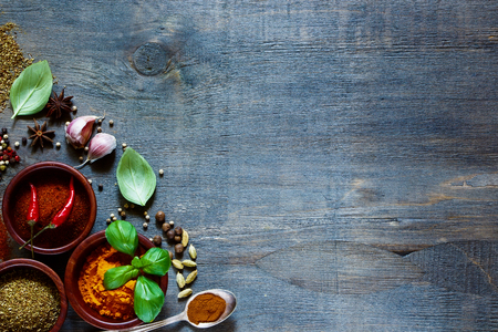 Top view of colorful  spices and herbs over dark old wood. Food and cuisine ingredients. Background with space for text. Stock Photo