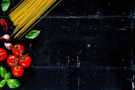 Espaguetis, hojas de albahaca y tomates con hierbas en el fondo oscuro de la vendimia con el espacio para el texto. La comida vegetariana, la dieta, la salud o el concepto de la cocina. Foto de archivo - 49746501