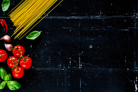 menu design: Spaghetti, basil leaves and tomatoes with herbs on dark vintage background with space for text. Vegetarian food, diet, health or cooking concept. Stock Photo