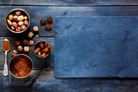製パン材料ナッツ、ココア パウダー、スパイス、バニラとシナモンの暗い木や石の質感を棒します。クリスマスと休日のコンセプトです。領域をコ