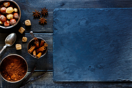christmas scent: Top view of aromatic spices and nuts for baking over dark wooden and stone background with space for text. Christmas and holidays concept.