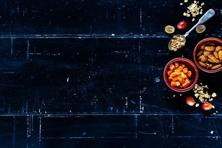 Gezonde muesli, noten en gedroogde vruchten op donkere uitstekende achtergrond met ruimte voor tekst. Gezondheid en voeding concept. Bovenaanzicht.