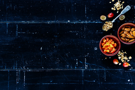 Healthy granola, nuts and dry fruits on dark vintage background with space for text. Health and diet concept. Top view.