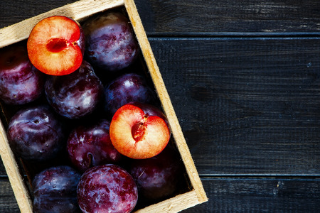 fond de texte: Close up of wooden box with plums over old dark board. Top view. Fruits background with space for text. Agriculture, Gardening, Harvest Concept.