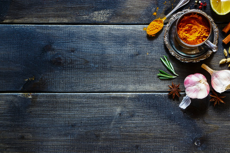 Fresh herbs and spices selection over old wood. Turmeric in a vintage cup on dark vintage background with space for text. Top view. Stockfoto