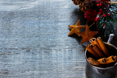 cinnamon sticks: Cinnamon sticks in vintage cup on wooden background for christmas.