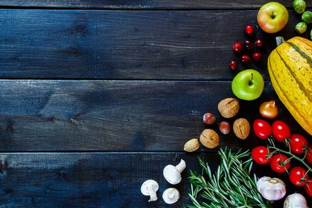 Groenten, fruit, noten en kruiden op donker hout. Gezonde voedselingrediëntenachtergrond met ruimte voor tekst. Gezondheid of dieet concept. Bovenaanzicht.