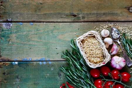 fresh: Food background with raw brown rice, fresh vegetables, spices and herbs over rustic wooden board. Cooking, healthy eating or vegetarian concept. Top view.