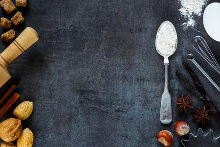 ナット、ビンテージ スプーン、麺棒、テキスト用のスペースと暗い金属を背景にベーキングのための芳香のスパイスの粉.クリスマスと休日のコンセ