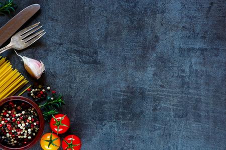 テキストのためのスペースと暗い金属を背景にハーブとトマトのスパゲッティ平面図です。バイオ健康的な食材。