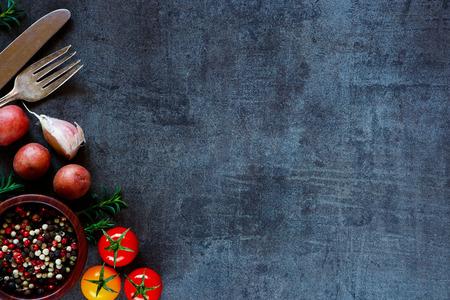 カラフルなスパイスやテキストのためのスペースと暗い金属を背景に料理の新鮮な野菜の平面図です。バイオ健康的な食材。 写真素材