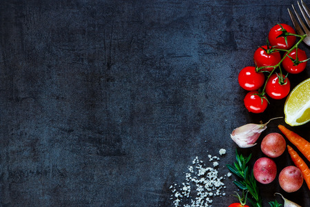 Close up of colorful spices and fresh vegetables for cooking on dark metal background with space for text. Top view. Bio Healthy food ingredients. Banco de Imagens