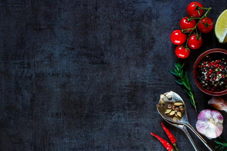 ビンテージ スプーン、テキスト用のスペースと暗い金属を背景に料理用の野菜。平面図です。バイオ健康的な食材。