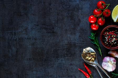 Vintage lepel en groenten voor het koken op dark metal achtergrond met ruimte voor tekst. Bovenaanzicht. Bio gezonde voedingsingrediënten.