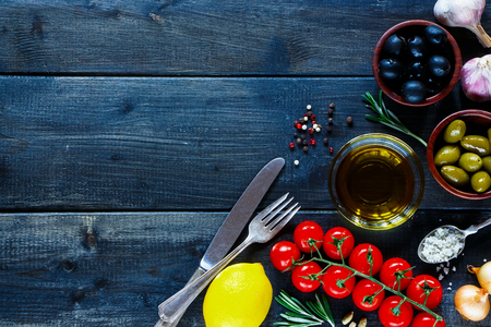 cooking oil: Italian ingredients for cooking (tomatoe, garlic, pepper, rosemary, olives, olive oil) on dark wooden background with space for text. Top view. Vegetarian food, health or cooking concept. Stock Photo