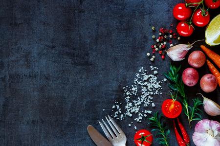 カラフルなスパイスやテキストのためのスペースと暗い金属を背景に料理の新鮮な野菜。平面図です。バイオ健康的な食材。