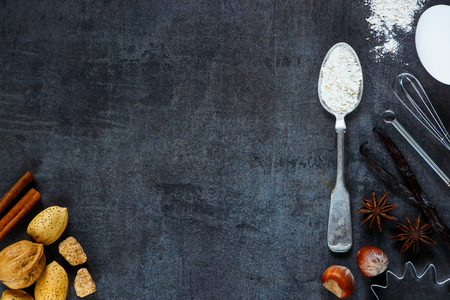 Whole flour in vintage spoon, nuts and aromatic spices for baking on dark metal background with space for text. Christmas and holidays concept. Top view. Healthy food ingredients.
