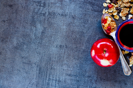 Delicious Breakfast on vintage table with cereal, red apple and coffee. Healthy eating, diet and cooking concept. Top view. Dark rustic background layout with free text space.