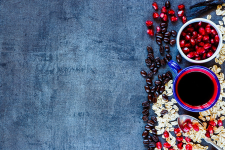 Coffee, oat flake and pomegranate for delicious Breakfast on vintage table. Healthy eating, diet and cooking concept. Top view. Dark rustic background layout with free text space.