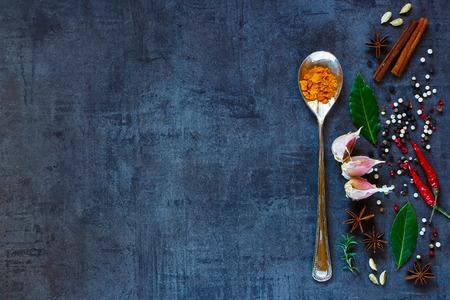 Bright specerijen op donkere uitstekende achtergrond met ruimte voor tekst. Kurkuma poeder in oude metalen lepel met kruiden en specerijen selectie. Gezond eten en koken concept. Bovenaanzicht. Dark rustieke stijl.