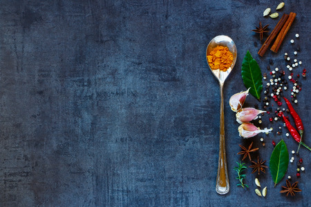 dark: Bright spices on dark vintage background with space for text. Turmeric powder in old metal spoon with herbs and spices selection. Healthy eating and cooking concept. Top view. Dark rustic style.