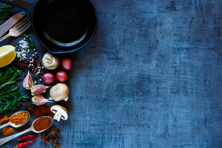 Bright spices and fresh vegetables on dark vintage background with space for text. Top view of herbs and spices selection. Healthy eating, vegetarian and cooking concept. Dark rustic style.