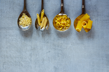 unboiled: Various mix of pasta in old metal spoons over vintage background with space for text. Healthy eating, diet and cooking concept. Top view. Rustic style.