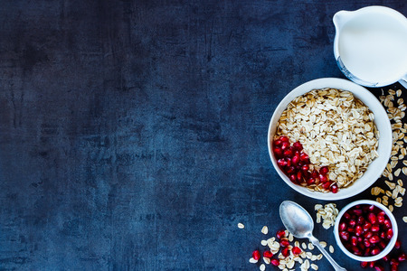 Healthy Breakfast on vintage background with space for text. Oat flake, pomegranate and fresh milk. Healthy eating, diet and cooking concept. Top view. Dark rustic style.