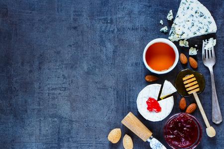 蜂蜜、フルーティーなジャム、暗いビンテージ テクスチャ上のナッツとチーズの様々 な。平面図です。フリー テキスト スペースの背景のレイアウ