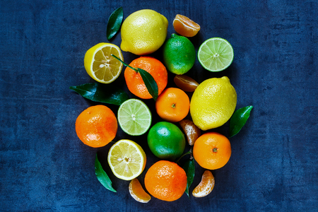 citrus: Assorted citrus fruits with leaves on dark vintage background. Agriculture, Gardening, Harvest Concept. Rustic background layout with free text space. Top view. Stock Photo