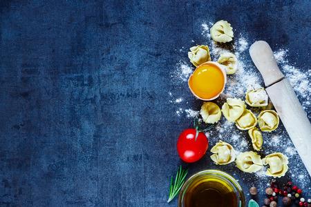 Gezond eten achtergrond met zelfgemaakte Italiaanse pasta tortellini, eieren, tomaten, meel, verse kruiden en olijfolie op donkere vintage textuur.