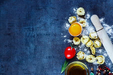Healthy eating background with homemade Italian pasta tortellini, egg, tomatoes, flour, fresh herbs and olive oil on dark vintage texture. Stock Photo - 54733451