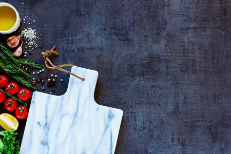 tablero: Cierre plano de deliciosos ingredientes y tabla de cortar mármol vacío para la cocina vegetariana y saludable. Vista superior. Espacio de la copia. Foto de archivo