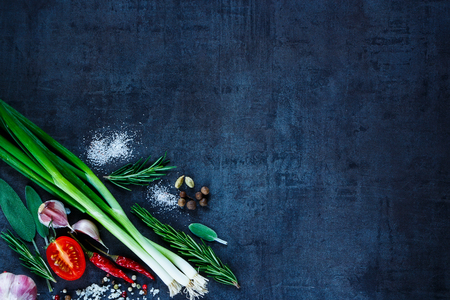 timber: Young green onions with peppercorns, tomato, garlic and rosemary on dark vintage background. Top view. Fresh organic vegetables.