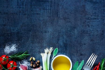Bovenaanzicht van olijfolie en verse koken ingrediënten (jonge groene uien, peperkorrels, tomaten, knoflook, rozemarijn) op een donkere uitstekende achtergrond. Bovenaanzicht.