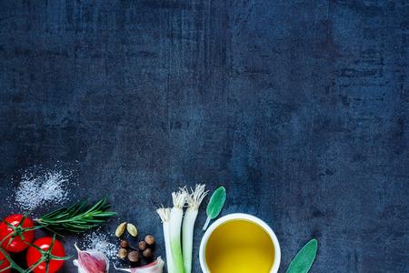 Olijfolie en verse koken ingrediënten (jonge groene uien, peperkorrels, tomaten, knoflook, rozemarijn) op een donkere uitstekende achtergrond. Bovenaanzicht.