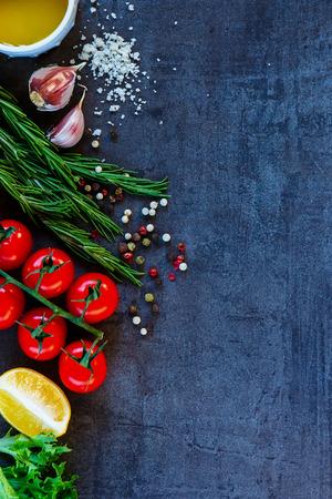 Delicious vegetables ingredients and seasoning for healthy vegetarian cooking on dark vintage background. Top view. Copy space.