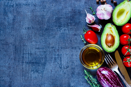 Top view of organic vegetables (tomatoes, avocado, eggplant, garlic, olive oil) on dark vintage background with space for text.