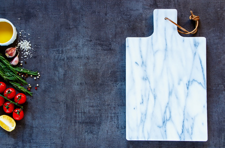 Delicious ingredients and empty marble cutting board for healthy vegetarian cooking.