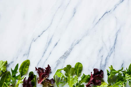 Fresh green lettuce on marble texture. Background layout with free text space. Top view. Фото со стока