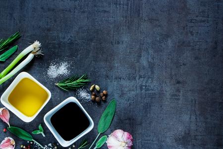 Essen Hintergrund mit Olivenöl, Essig, Pfeffer, Meersalz, Knoblauch und Rosmarin auf dunklem Vintage Textur. Draufsicht. Kräuter und Gewürze Auswahl.